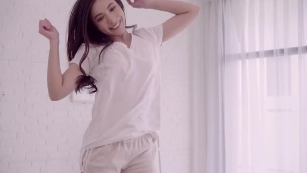 Cheerful happy young Asian woman with headphones dancing while listening music on bed in her bedroom. Lifestyle woman relax at home.