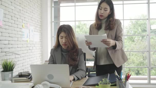 Attractive smart Asian business woman in smart casual wear working on laptop while sitting on desk while her angry manager standing angry throwing papers on office desk. Women work at office concept.