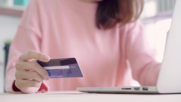 Krásná asijská žena pomocí počítače nebo notebooku nákup online nákupy kreditní kartou při nošení svetr sedí na stole v obývacím pokoji doma. Životní styl žena domácí koncept.