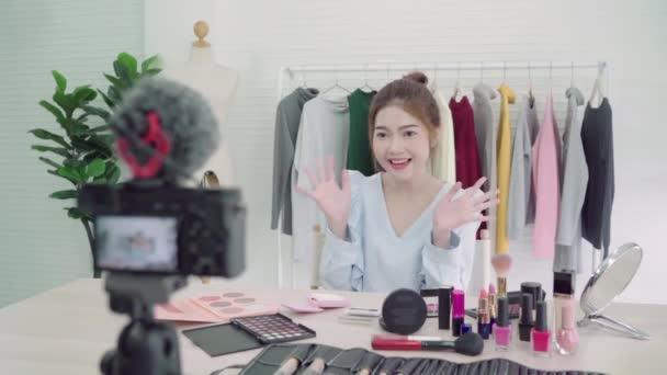 Blogerka prezentovat krása kosmetika sedí v přední kamerou pro nahrávání videa. Krásné asijské ženy používají kosmetiku, zatímco kontrola make-upu kurz živé vysílání videa na sociální sítě Internet.