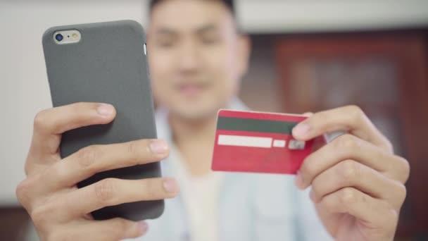 Ázsiai ember használ smartphone online vásárlás és hitelkártyáját az internet otthon a nappaliban. Asia férfi alkalmi ruhák az asztalnál ül, pihentető és vásárol árukat könnyen. E kereskedelmi fogalmak.