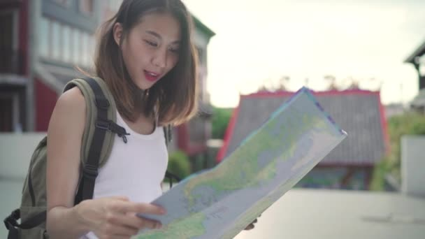 Cheerful beautiful young Asian backpacker woman direction and looking on location map while traveling at Chinatown in Beijing, China. Lifestyle backpack tourist travel holiday concept.