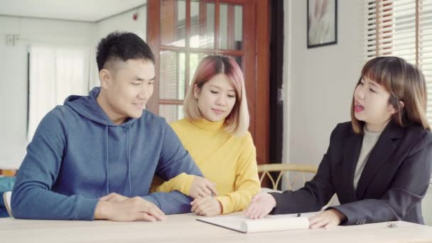 Šťastný mladý asijský pár a realitní agent. Veselý mladý muž podepisování některé dokumenty při sezení u stolu spolu se svou ženou. Nákup nové nemovitosti domu. Podpisu smlouvy o dobrém stavu.