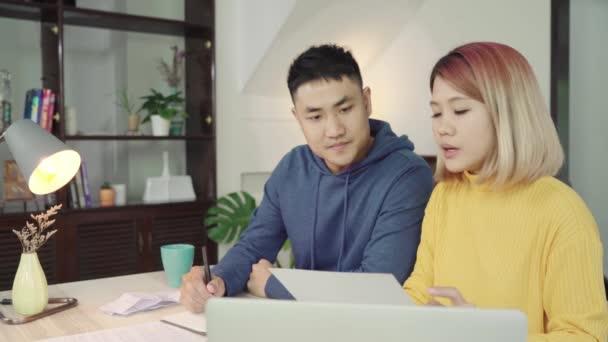 Fiatal ázsiai pár pénzügyek, felülvizsgálja a bank számlák segítségével a laptop számítógép és a számológép modern otthon kezelésére. Nő és férfi csinál íróasztali munka együtt, a kifizető adó online notebook PC.
