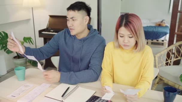 Mladí zdůraznil asijský pár, Správa financí, kontrola jejich bankovní účty pomocí přenosného počítače a Kalkulačka v moderní domov. Žena a muž dělá papíry pohromadě, platící daně online.