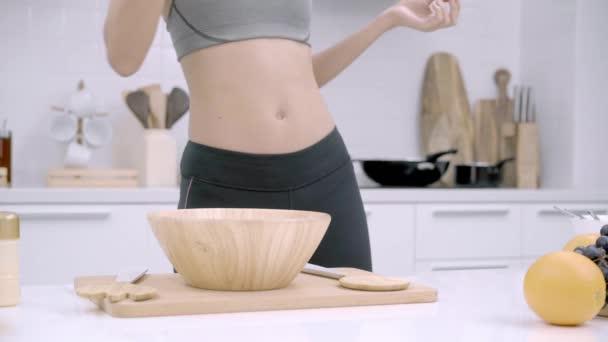 Mladá asijská žena pít pomerančový džus dělat salát v kuchyni, krásná žena v sportovní oblečení použití bio ovoce a zeleninu, aby zdravé potraviny sama doma. Zdravé jídlo koncept.