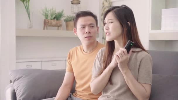Asian couple argue while watching TV in living room at home, sweet couple have angry moment while lying on the sofa when relax at home. Lifestyle couple relax at home concept.
