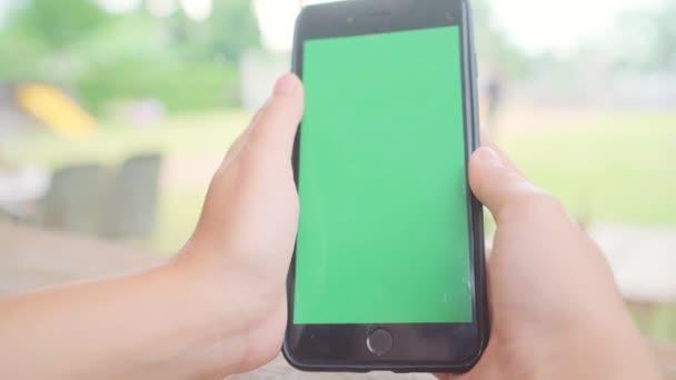 junge Asiatin mit schwarzem Mobiltelefon mit grünem Bildschirm. asiatische Frau mit Smartphone, blättert Seiten, während sie im Café sitzt. Chroma-Schlüssel.