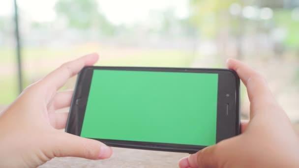 Mladá asijská žena černý mobilní telefon zařízení pomocí zeleným plátnem. Asijské žena držící smartphone, rolování stránky při posezení v kavárně. Chroma klíč.
