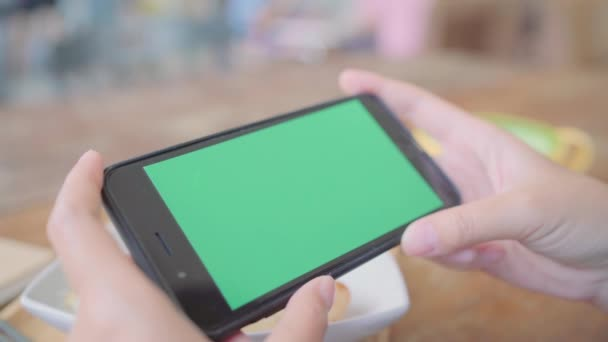 Junge Asiatin mit schwarzen Handy-Gerät mit Greenscreen. Asiatische Frau mit Smartphone, Seiten blättern, während Sie im Café sitzen. Chroma-key.