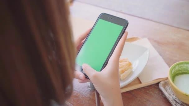 Fiatal ázsiai nő fekete mobiltelefon-készülék segítségével a zöld képernyő. Ázsiai nő gazdaság smartphone, görgetés oldalak kávézóban ülve. Chroma-kulcs.