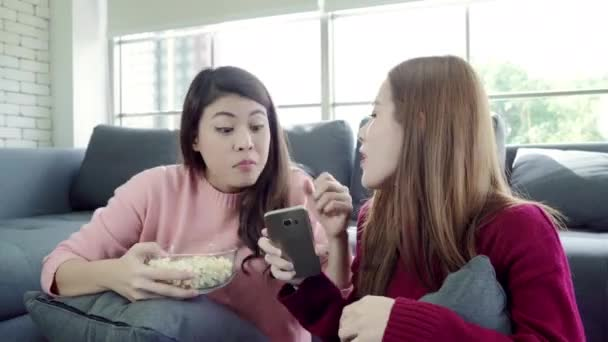 Asian women playing pillow fight and eating popcorn in living room at home, group of roommate friend enjoy funny moment while lying on the sofa. Lifestyle women relax at home concept.