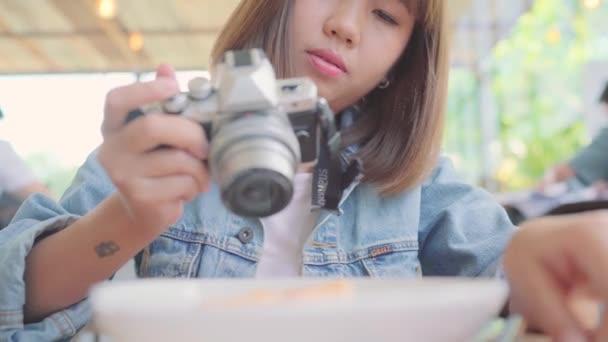 Foodbloggerin asiatische Frau mit Kamera für Foto-Dessert, Brot und Trinken, während sie auf dem Tisch im Café sitzt. Lifestyle Schöne Frauen entspannen sich im Café.