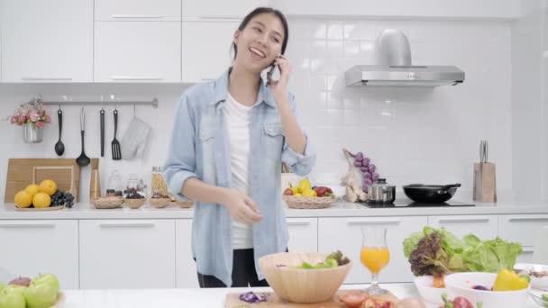 Mladá asijská žena dělat salát zdravých potravin a mluví na smartphone v kuchyni, krásné ženské použití bio zeleninu připravovat doma. Životní styl žen odpočívat doma koncept.