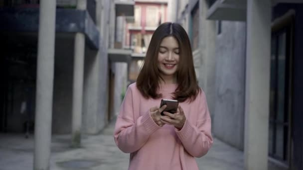Slow motion - Asian tourist blogger woman using smartphone for direction and looking on location map while traveling at Chinatown in Beijing, China. Lifestyle backpack tourist travel holiday concept.