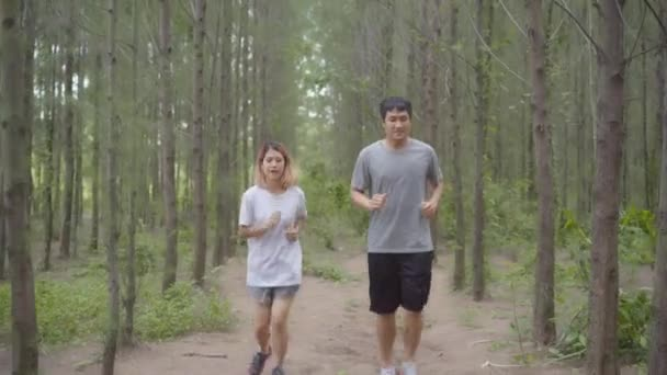 Healthy young athletic sporty Asian runner man and woman in sports clothing running and jogging on forest trail. Lifestyle fit and active women exercise in the forest concept.