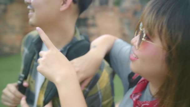 Slow motion - Traveler Asian couple spending holiday trip at Ayutthaya, Thailand, backpacker sweet couple enjoy their journey at amazing landmark in traditional city. Lifestyle couple travel concept.