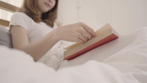 Krásná mladá asijská žena čte knihu vleže na posteli, Žena spát po odpočívat v pokoji doma. Životní styl žen užívajících uvolnit čas na domácí koncept.