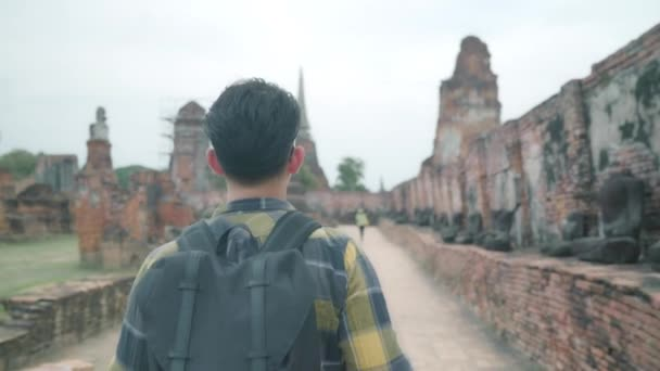 Traveler Asian man spending holiday trip at Ayutthaya, Thailand, backpacker male enjoy his journey at amazing landmark in traditional city. Lifestyle men travel holidays concept.