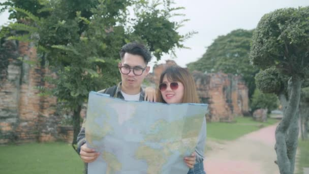 Traveler Asian couple direction and looking on location map while spending holiday trip at Ayutthaya, Thailand, backpacker couple enjoy journey in traditional city. Lifestyle couple travel concept.