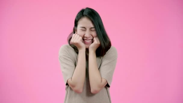 Smiling adorable Asian female with positive expression, smiles broadly, dressed in casual clothing and looking at the camera over pink background. Happy adorable glad woman rejoices success.