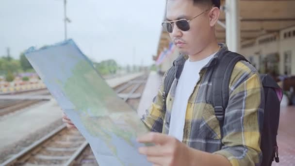 Traveler Asian man direction and looking on location map while spending holiday trip and waiting train at train station, Young male tourist backpacker enjoy journey. Lifestyle men travel concept.