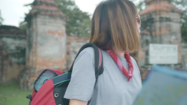 Traveler Asian woman direction and looking on location map while spending holiday trip at Ayutthaya, Thailand, backpacker female enjoy journey in traditional city. Lifestyle women travel concept.