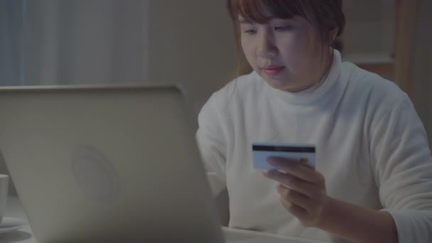 schöne asiatische Frau mit Laptop Online-Shopping per Kreditkarte kaufen, während lässig auf dem Schreibtisch im Wohnzimmer in der Nacht zu Hause sitzen. Lifestyle-Frauen im Homeoffice-Konzept.