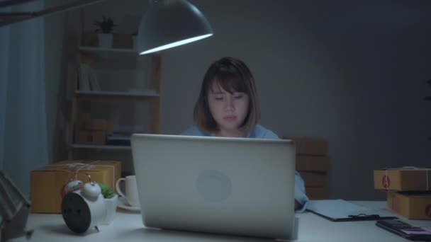 Young Asian entrepreneur business woman owner of SME online checking product on stock and save to laptop working in night at home. Feeling sick and tired. Small business owner at home office concept.
