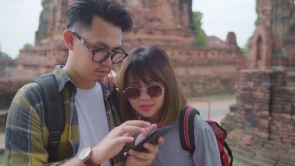 Traveler Asian couple using smartphone for direction and looking on location map while spending holiday trip at Ayutthaya, Thailand, backpacker sweet couple enjoy journey in traditional city.