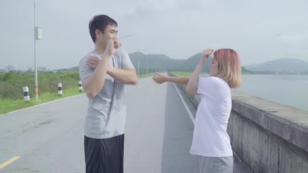 Asian runner couple legs warming and stretching her arms to ready for running on street, Healthy young sweet couple exercise near lake. Lifestyle fit and active couple exercise on street concept.
