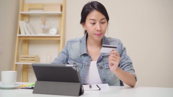 schöne asiatische Frau mit Tablet Online-Shopping per Kreditkarte kaufen, während lässig auf dem Schreibtisch im Wohnzimmer zu Hause sitzen. Lifestyle-Frauen arbeiten zu Hause.