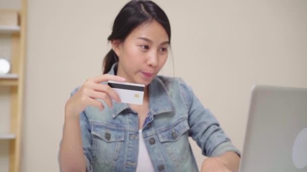 schöne asiatische Frau mit Laptop Online-Shopping per Kreditkarte kaufen, während lässig auf dem Schreibtisch im Wohnzimmer zu Hause sitzen. Lifestyle-Frauen arbeiten zu Hause.