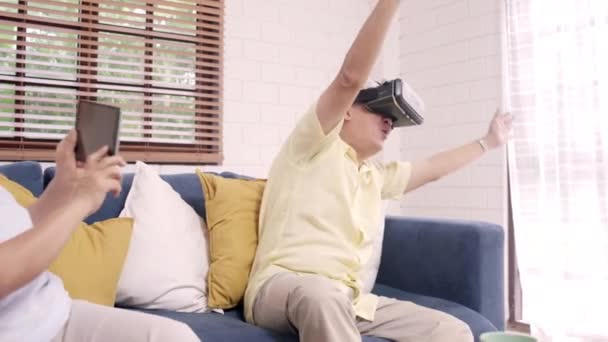 Asian elderly couple using tablet and virtual reality simulator playing games in living room, couple feeling happy using time together lying on sofa at home. Lifestyle Senior family at home concept.