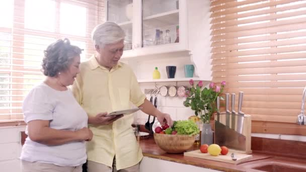 Asian elderly couple using tablet prepare ingredient for making food in the kitchen, Couple use organic vegetable for healthy food at home. Lifestyle senior family making food at home concept.