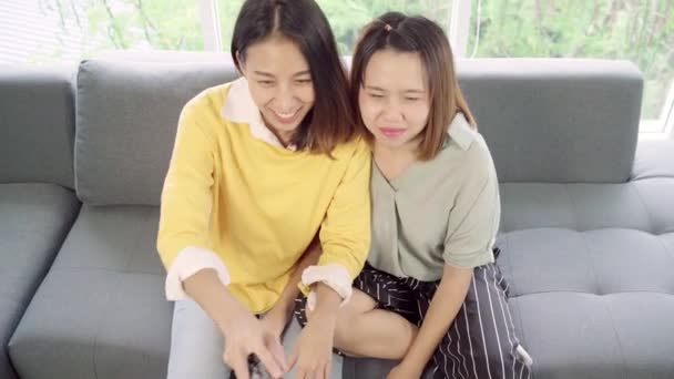 Asijské ženy fandí fotbalovému utkání před televizí doma, legrační kamarádi si užijí vtipnou chvíli, když leží na pohovce, když odpočívejte doma. Životní styl ženy relaxační v domácí koncepci.