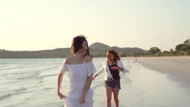 Mladý asijský lesbický pár, co běží na pláži. Krásné ženy s radostí Relaxujte na pláži blízko moře, když večer zapadne. Životní styl lesbický pár cestování po pláži.