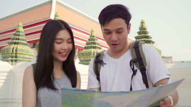 Traveler Asian couple direction on location map in Bangkok, Thailand, sweet Asia couple looking on map find landmark while spending holiday trip. Lifestyle couple travel in city concept.