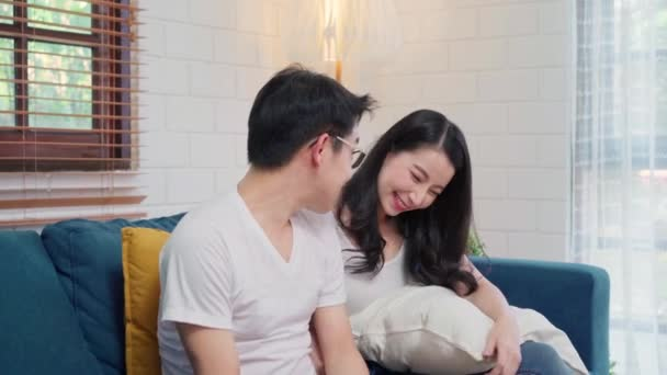 Asian couple hug together in living room at home, sweet couple enjoy love moment while lying on the sofa when relaxed at home. Lifestyle couple relax at home concept.