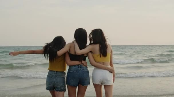 Group of Asian young women walking on beach, friends happy relax having fun playing on beach near sea when sunset in evening. Lifestyle friends travel holiday vacation summer concept. Slow motion shot