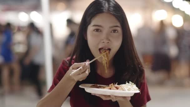 asiatische junge Frau reisen in Bangkok, Thailand, schöne Frau glücklich zu Fuß und essen Pad Thai an der Khao san Straße. Frauen, die reisen, essen Streetfood im thailändischen Konzept. Zeitlupenaufnahme.