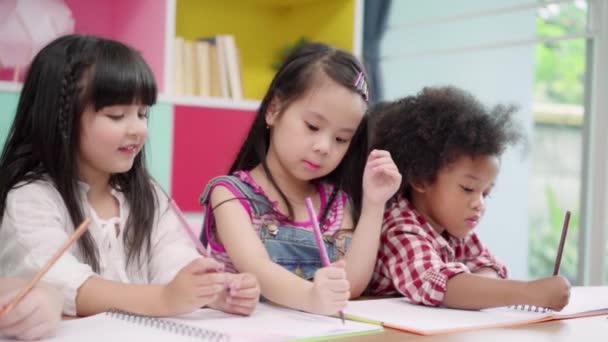 Pomalý pohyb-skupina dětí kreslené v učebně, mladí víceetnické mladíci a dívky šťastné a zábavné studium a hraní na papíře na základní škole. Děti kreslením a malováním ve školní koncepci.