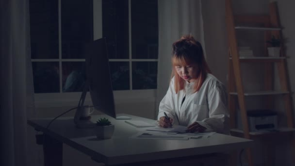 Young asian woman working late using desktop on desk in living room at home. Asia business woman writing notebook document finance and calculator in night at home office. Overworked female concept.
