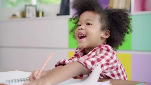 Africké děti kreslou a dělají domácí úkoly v učebně, mladá dívka je šťastná a hraje si na papíře na základní škole. Dětský kreslením a malování na školní koncepci.