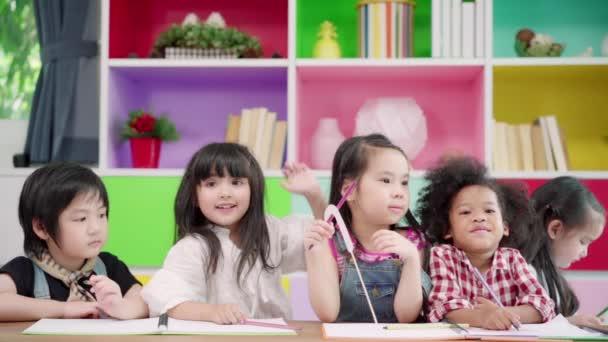 Zeitlupe - eine Gruppe von Kindern, die im Klassenzimmer zeichnen, multiethnische Jungen und Mädchen, die in der Grundschule fröhlich lernen und malen. Kinder zeichnen und malen im Schulkonzept.