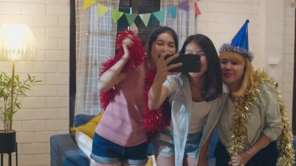 Group of Asian women party at home, female using mobile phone making vlog  selfie to social media while funny dance together in living room in night   Young friend celebrate holiday concept  Slow motion