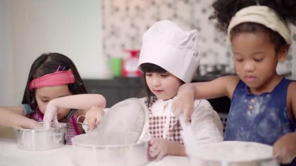 Slow motion - Group of children baking cake together in classroom, Multi-ethnic young boys and girls happy making dessert cooking in kitchen at school. Kids cooking at school concept.