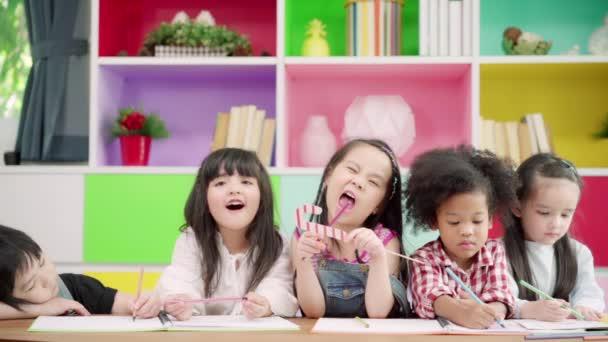 Lassú mozgás-gyermekcsoport rajz az osztályban, többnemzetiségű fiatal fiúk és lányok boldog vicces tanulmány és játék festmény papíron az elemi iskolában. Gyerekek rajza és festése az iskolai koncepcióban.