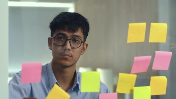 Ázsiai kreatív ember kibír egy ragacsos jegyzetet üvegtábla. Fiatal szakmai üzleti férfi írási információ, stratégia, emlékeztető papíron, üzleti helyzet, indítás Loft irodai koncepció.