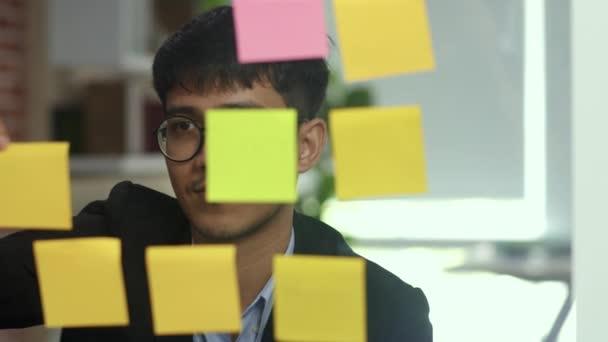Ázsiai kreatív ember kibír egy ragacsos jegyzetet üvegtábla. Fiatal szakmai üzleti férfi írni információkat, stratégia, emlékeztető papírra, üzleti helyzet, indítás Loft irodai koncepció. Lassított mozgás.